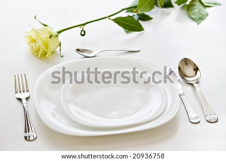 place setting with white plates and beige  rose flower - stock photo