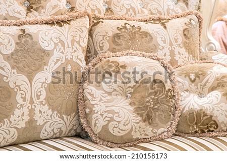Place several pillows on the sofa in cream. - stock photo