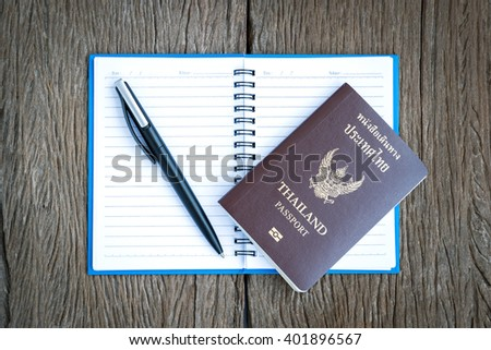 Place the pen and Thailand passport on a blank page of a notebook on old wooden background. - stock photo