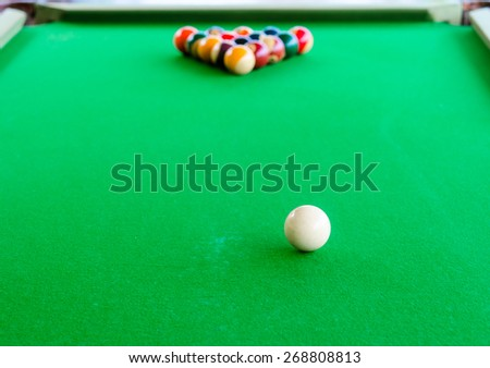 Placement of billiard balls on the table before the game. Focus on white ball. - stock photo