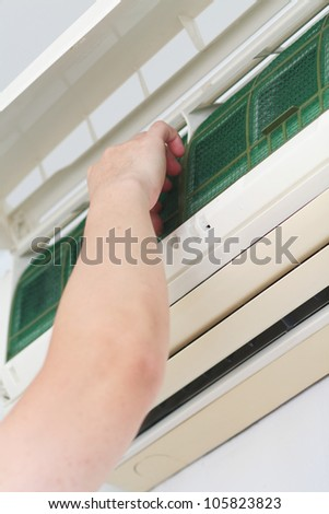 Placing back clean filter into air-conditioner - stock photo