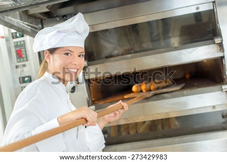 Placing bread in the oven - stock photo