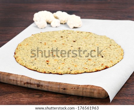 Plain cauliflower pizza crust on a piece of parchment paper on a cutting board.  Selective focus on front edge of crust. - stock photo