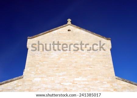 Plain facade of a monastery over a dramatic blue sky - stock photo