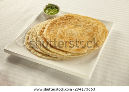 Plain paratha puri served with freshly diced corriander in green chutney - stock photo