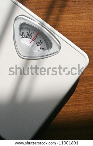 Plain white bathroom scale on a wood floor. Vertically framed shot - stock photo