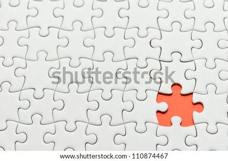 Plain white jigsaw puzzle, on orange background. - stock photo