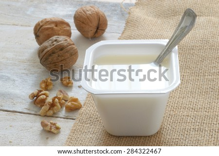 Plain yogurt on a sack cloth with some nuts served in a wooden white table of a rustic kitchen. - stock photo