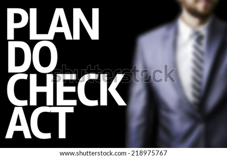Plan Do Check Act written on a board with a business man on background - stock photo