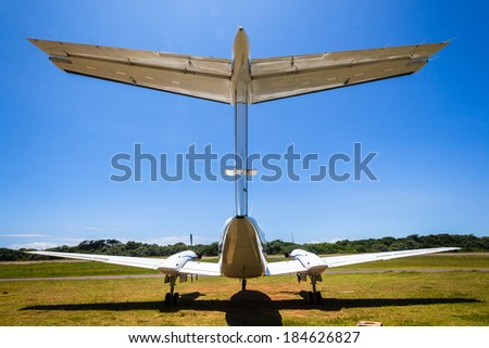 Plane Aircraft Tail Wing Blue Back of prop twin engine aircraft tail wing six seater in blue sky - stock photo