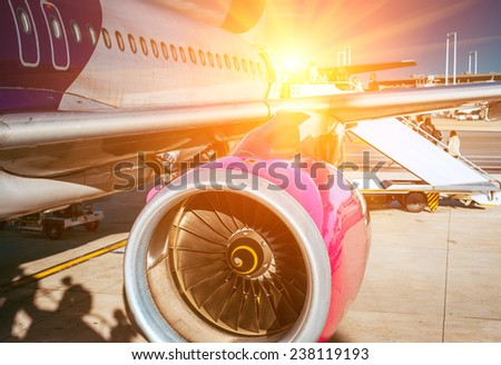 plane and the airport in the setting sun - stock photo