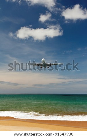 plane comes in to land on a tropical beach - stock photo