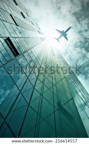 plane flying over a modern glass and steel office building in Frankfurt am Main, Germany - stock photo