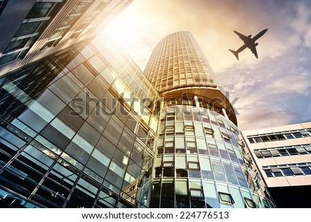 plane flying over modern office tower - stock photo
