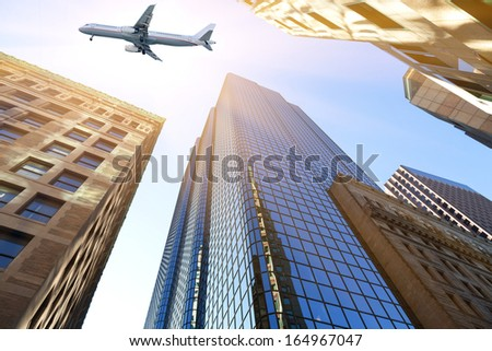 plane flying over skyscrapers - stock photo