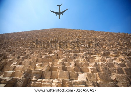plane flying over the pyramids of Giza. The cultural heritage of humanity - stock photo