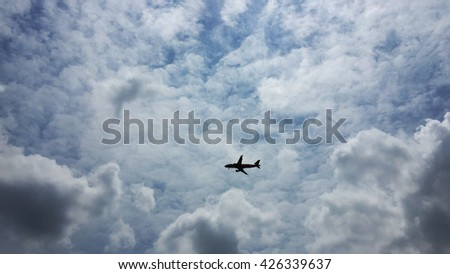 plane in most cloudy blue sky vignette - stock photo
