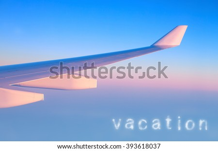 Plane in the air, wing of a great aeroplane over blue pink sky background, business trip, travel and vacation concept - stock photo