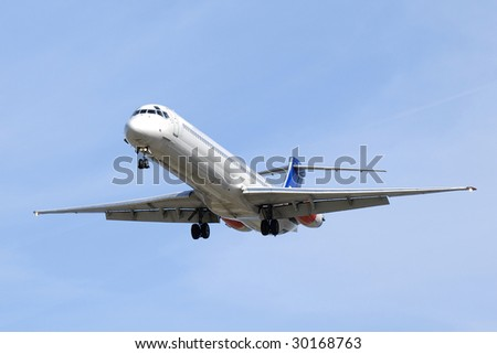 Plane is going to land in an airport. Blue sky. - stock photo