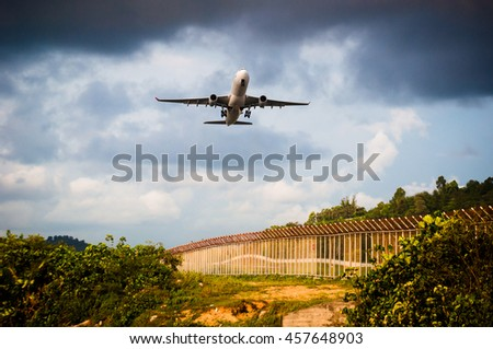 plane is take off to sky from airport and over plant, tree and fence among warm light - stock photo