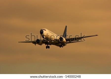 Plane landing against sunset sky - stock photo
