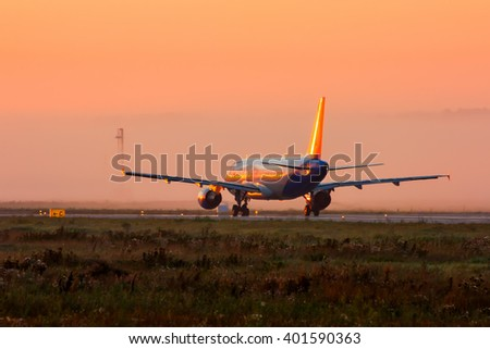 Plane on the runway in the early foggy morning - stock photo