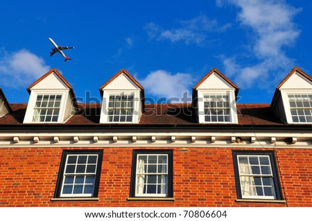 Plane over old georgian house in London - stock photo
