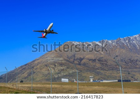 plane taking off the international Queenstown airport. New Zealand - stock photo