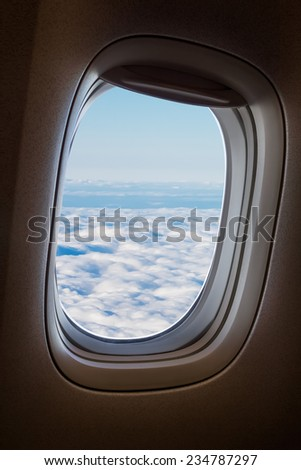 Plane window with blue sky and clouds outside. - stock photo