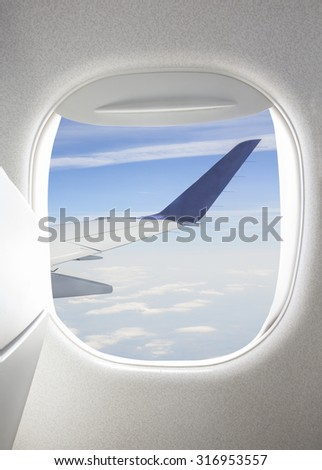 Plane window with view of sky and wing - stock photo