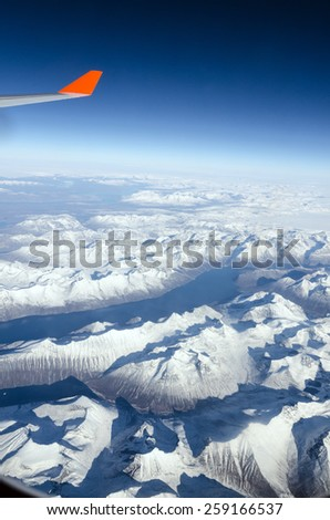 Plane wing, white clouds, blue sky and ground - stock photo
