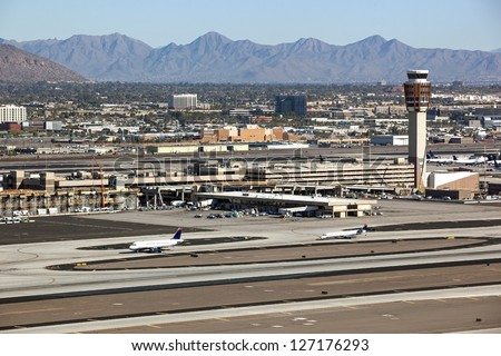 Planes and construction on commuter train bridge at busy southwest international airport - stock photo