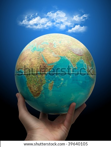 Planet earth holding in hand with clouds above.Weather concept - stock photo