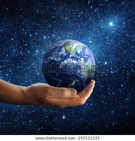 Planet earth on palm and space background. Conceptual Image. Elements of this image furnished by NASA - stock photo