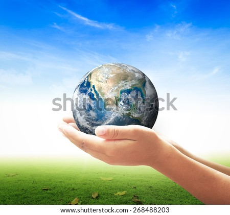 Planet in human hands on nature background. environment concept. Elements of this image furnished by NASA. - stock photo