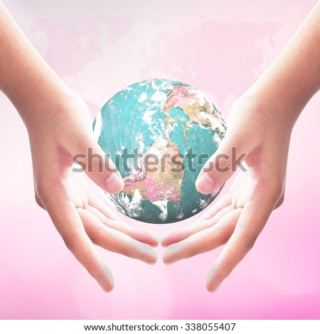 Planet in human hands on world map of cloud beautiful pink nature background. Donation Charity Love Right Cancer Nurses CSR Map Youth Service Ovarian concept. Elements of this image furnished by NASA - stock photo