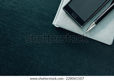 Planner with phone on a black background. - stock photo