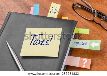 Planner with sticky note - Taxes - stock photo