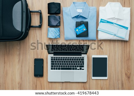 Planning a business trip: bag, formal clothing, credit cards and plane tickets on a desk with laptop, smartphone and tablet, traveling and technology concept - stock photo