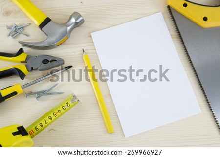 Planning a Project in Carpentry and Woodwork Industry with paper sheet, saw and a sego of tools - stock photo
