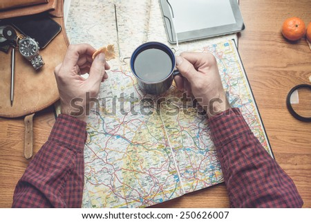 Planning a travel destination. toned image, focus on hand with a cup - stock photo
