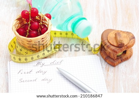 Planning of a diet. A notebook with inscription - My Diet, a measuring tape, water and red currant  - stock photo