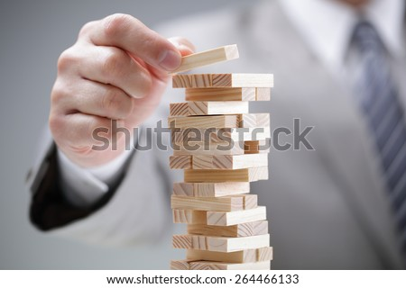 Planning, risk and strategy in business, businessman gambling placing wooden block on a tower - stock photo