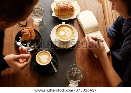 Planning session at a cafe between two people with coffee - stock photo