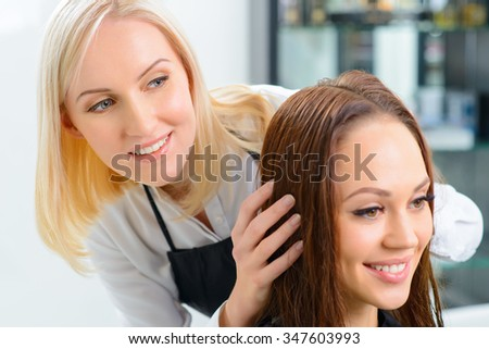 Planning the hairstyle. Young professional stylist is occupied with her client. - stock photo