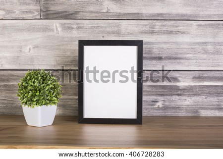 Plant in pot and blank picture frame on wooden surface. Mock up - stock photo