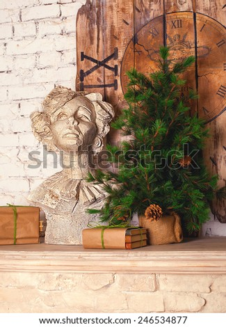 Plaster bust, fur tree with cones, vintage wood clock decor standing on the fireplace mantel - stock photo