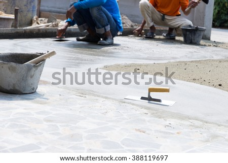 Plaster concrete floor with workers on construction sites. - stock photo