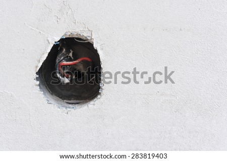 Plastered wall with exposed wires in wall socket  - stock photo