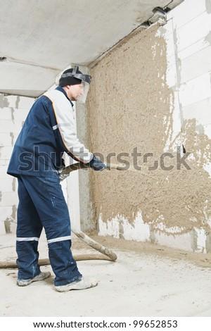 Plasterer at indoor wall renovation decoration spraying liquid plaster from plastering station - stock photo